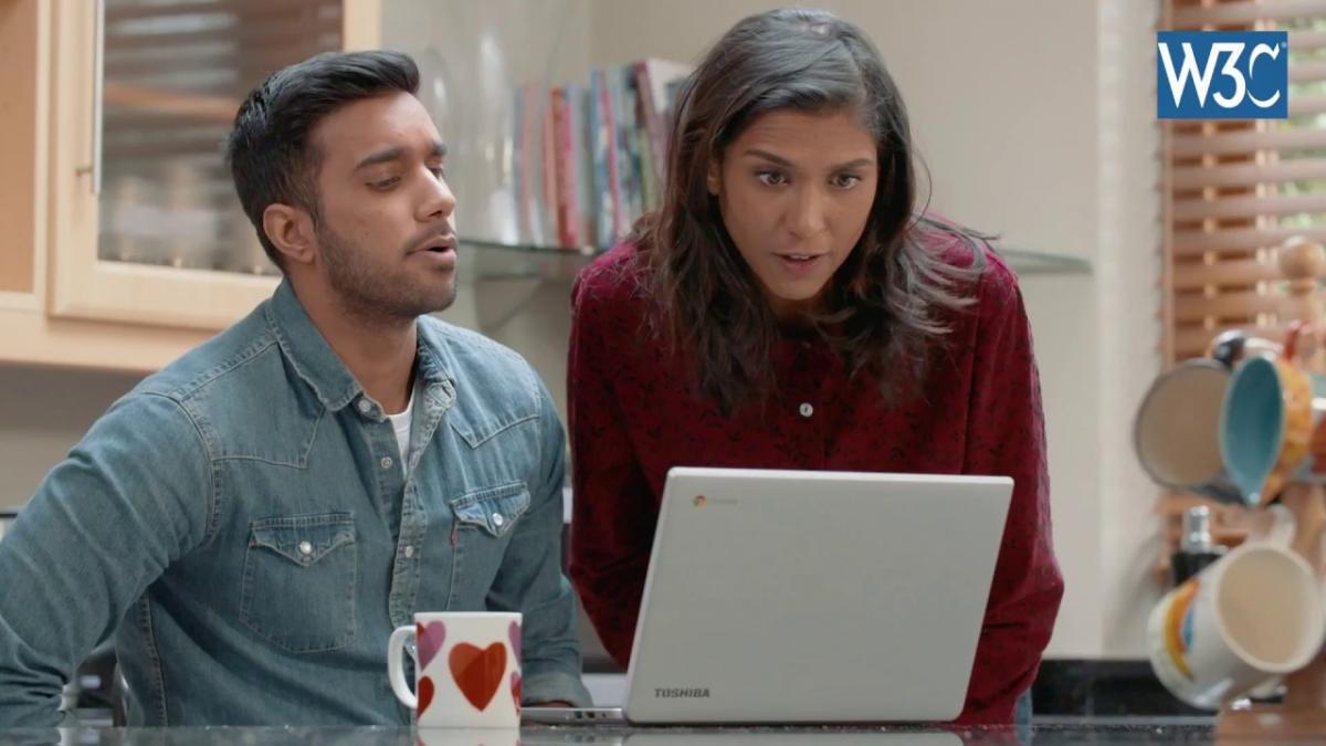 Beeld uit een video van twee mensen die praten tijdens het kijken naar een computerscherm.
